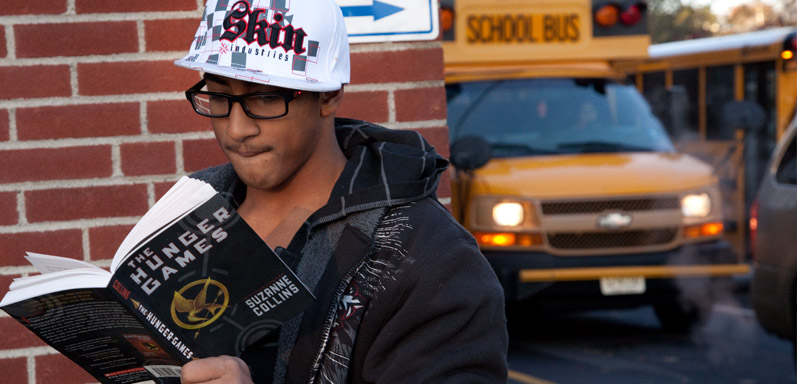 High School student reading as he gets off the bus in the morning