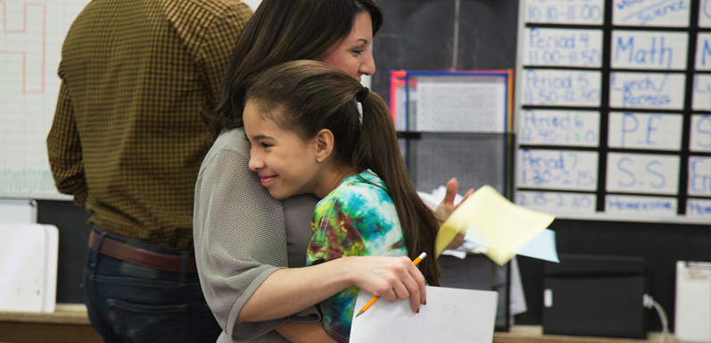 Chapel Hill Academy female student and teacher embracing