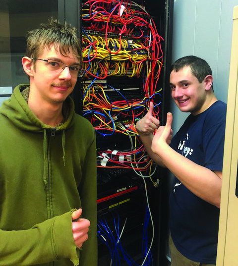 Two Chapel Hill Academy male students working with a server rack and giving thumbs up hand signals