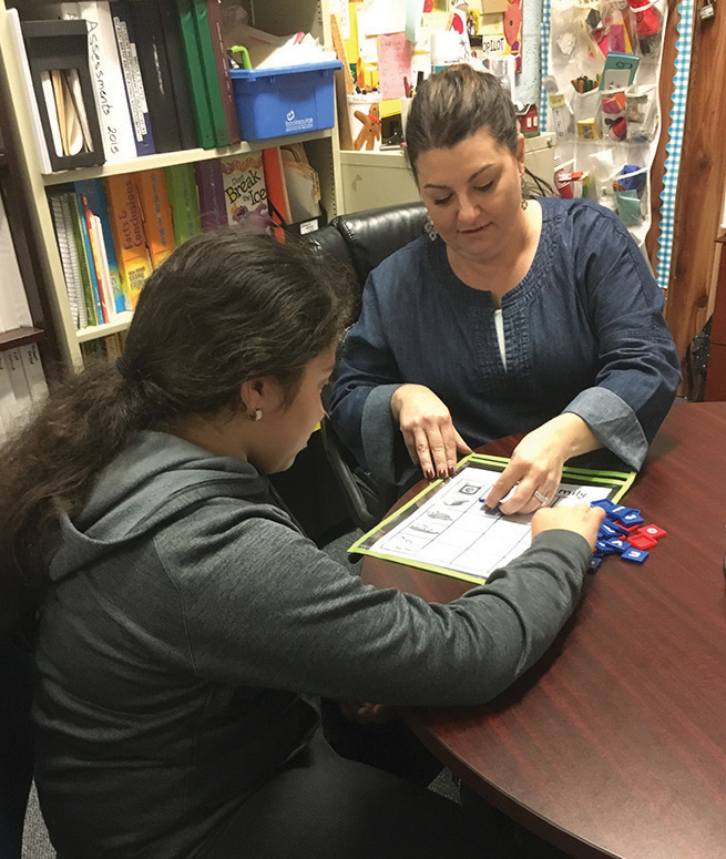 Female CHA middle school student working on reading with a female teacher